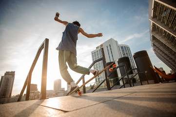 Young active man jumping on skateboard against the city buildings