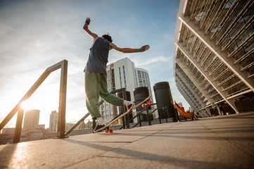 Back view of young active man jumping on skateboard against the city buildings