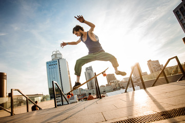 Active young man jumping on skateboard against the city buildings and sky