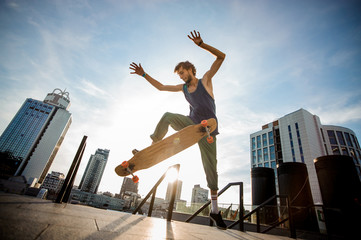 Young skateboarder jumping on board against city buildings