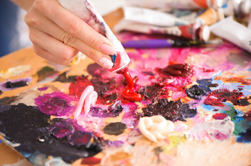 Closeup of paintbrush in woman hands mixing paints on palette