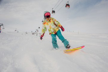 Young girl running on the snowboard in the mountain resort