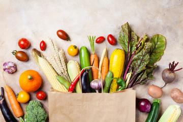 Photo sur Plexiglas Legume Autumn vegetables in shopping paper bag on kitchen table top view.
