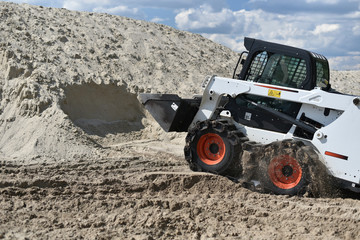 skid-steer loader working with sand