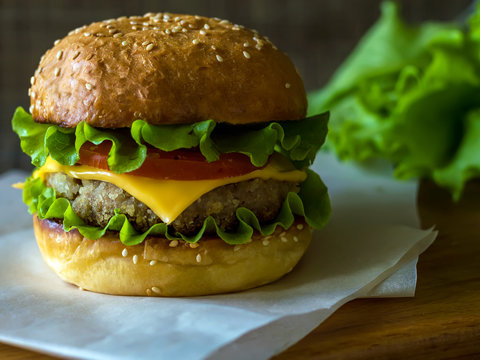Hamburger is big. Cheeseburger's on the table. The unhealthy food. The concept of healthy eating.