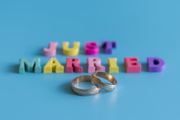 Multicolored inscription just married on a blue background