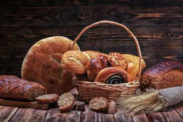 Ciabatta, lavash, buns and other bakery products lie on a wooden rustic table on a dark background.