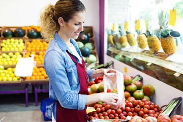 Young saleswoman selecting fresh tomatoes in health grocery shop.