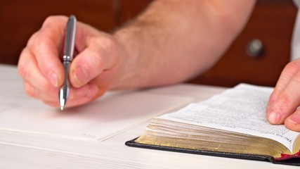 Man is holding a pen in his hand with an open book lying in fornt of him