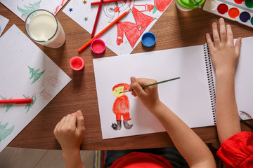 Little child drawing picture at table, top view. Christmas celebration
