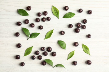 Flat lay composition with fresh acai berries and leaves on wooden background