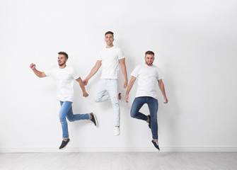 Group of young men in jeans jumping near light wall