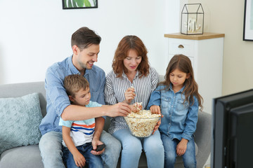 Family watching TV with popcorn in room