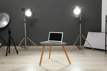 Interior of modern photo studio with laptop, table and professional equipment
