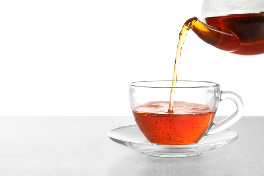 Pouring hot tea into glass cup on white background