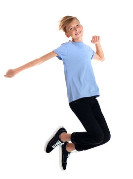 Portrait of young boy jumping on white background