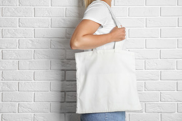 Woman with tote bag near brick wall. Mock up for design