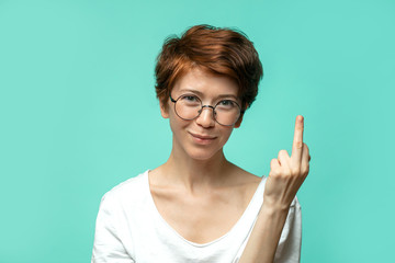 Head shot of ironic irritated red haired female smiling at camera and shows middle finger in discontent, refuses to participate in doubtful deal, poses against blue background.