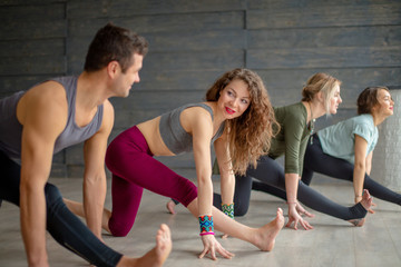 Young women and man doing flexibility exercise, stetching legs, yoga practice indoors over grey studio background, sportive man standing on foreground.