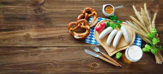 Bavarian sausages with pretzels, sweet mustard and beer on rustic wooden table