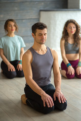 Handsome young muscular man, yogi teacher conducting yoga to caucasian women. Group training. Healthy lifestyle concept.