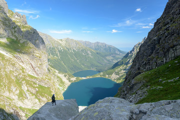 Hikers ejoy the view of the  of Czarny Staw pod Rysami and Morskie Oko lakes in the High Tatra Mountains.