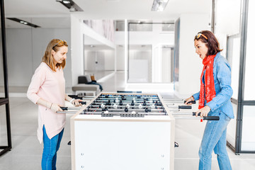 Two girls friends playing table football mini game indoors