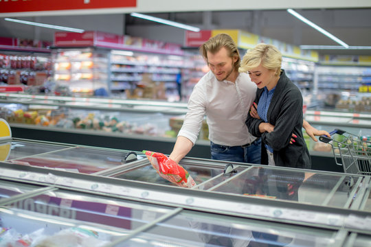 Cute caucasian adult couple choose frozen foods from the supermarket refrigerator. Family shopping at a big trading centre in a grocery department.