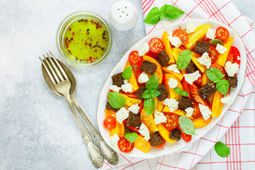 Delicious summer salad of yellow and red tomatoes, croutons, cheese mozzarella,  Basil and olive oil