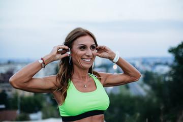 Professional female athlete preparing headphones before the run