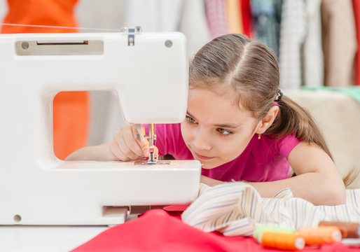 Little girl prepares a sewing machine for work, inserts a thread. Hobby sewing as a small business concept