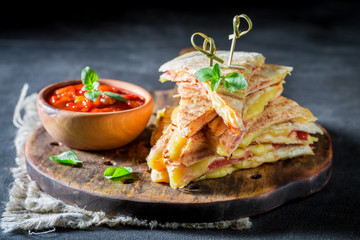 Closeup of tasty quesadilla with sauce and herbs