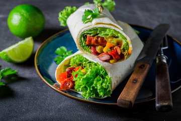 Closeup of burrito with spicy salsa and lime