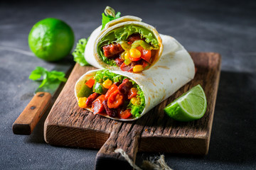 Tasty burrito with spicy salsa and fresh lime
