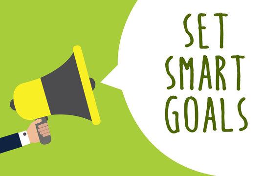 Conceptual hand writing showing Set Smart Goals. Business photo showcasing Establish achievable objectives Make good business plans Man holding loudspeaker speech bubble message speaking loud.