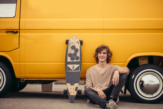 Young hipster guy sitting next his yellow car during road trip
