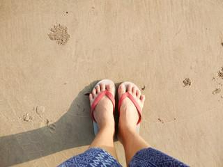 Female Feet Wear Sandals on the sand beach