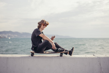 Young man using a cellphone while sitting at longboard on pier witth yacht