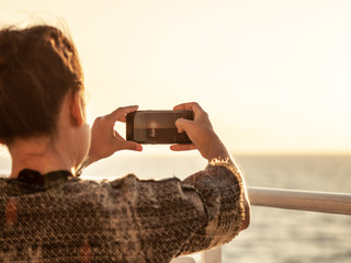 Cruise ship vacation young woman enjoying sunrise on travel at sea. Taking pictures of the ocean on a ferry.
