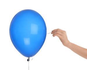 Woman piercing blue balloon on white background