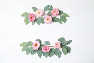 Fresh eucalyptus leaves with flowers and space for design on white wooden background, flat lay
