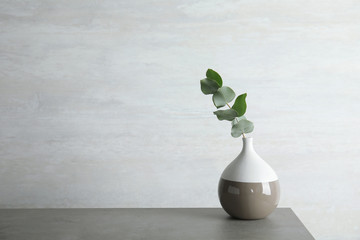 Vase with eucalyptus branch with fresh leaves on table