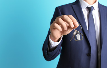 Real estate agent holding key on color background, closeup