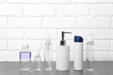 Different cosmetic products on table against brick wall