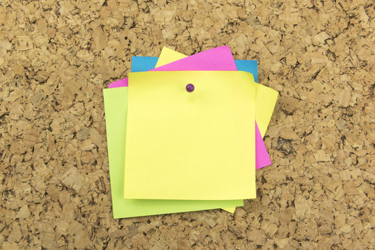 Yellow post it notes with pin  posted to a cork board