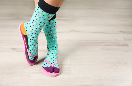 Woman wearing bright socks with flip-flops standing on floor. Space for design