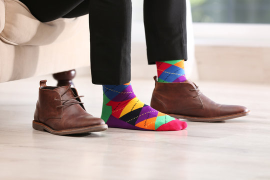 Man in stylish socks and one shoe on couch indoors, closeup