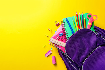 Flat lay composition with backpack and school stationery on color background