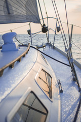 Sailing at sunset. A view from the yacht's deck to the bow and sails. Close-up. Baltic sea, Latvia
