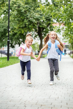 Funny children run from school with backpacks. The concept of school, study, education, friendship, childhood.